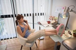 mulher de pernas pro ar trabalhando em casa
